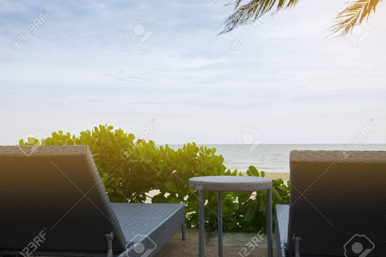 Immagini Stock - Sedie A Sdraio Con Tavolo Sulla Spiaggia Sotto La ...