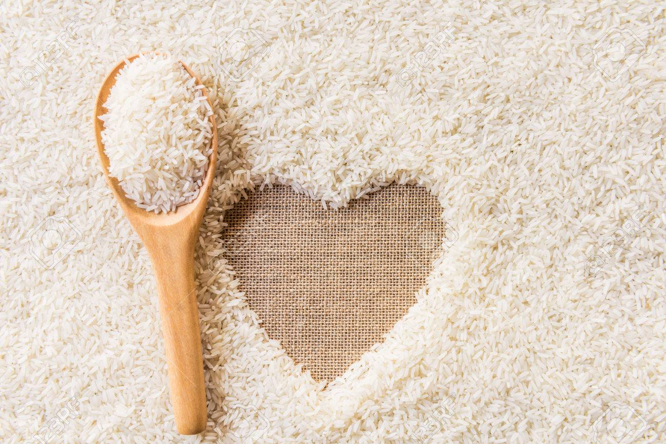 rice in wooden Spoon on rice background Space in the middle of a heart. sackcloth is background - 36967723