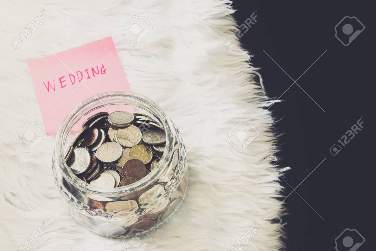 many coins in a money jar with wedding label on jar. wedding concept. saving concept - 39280144