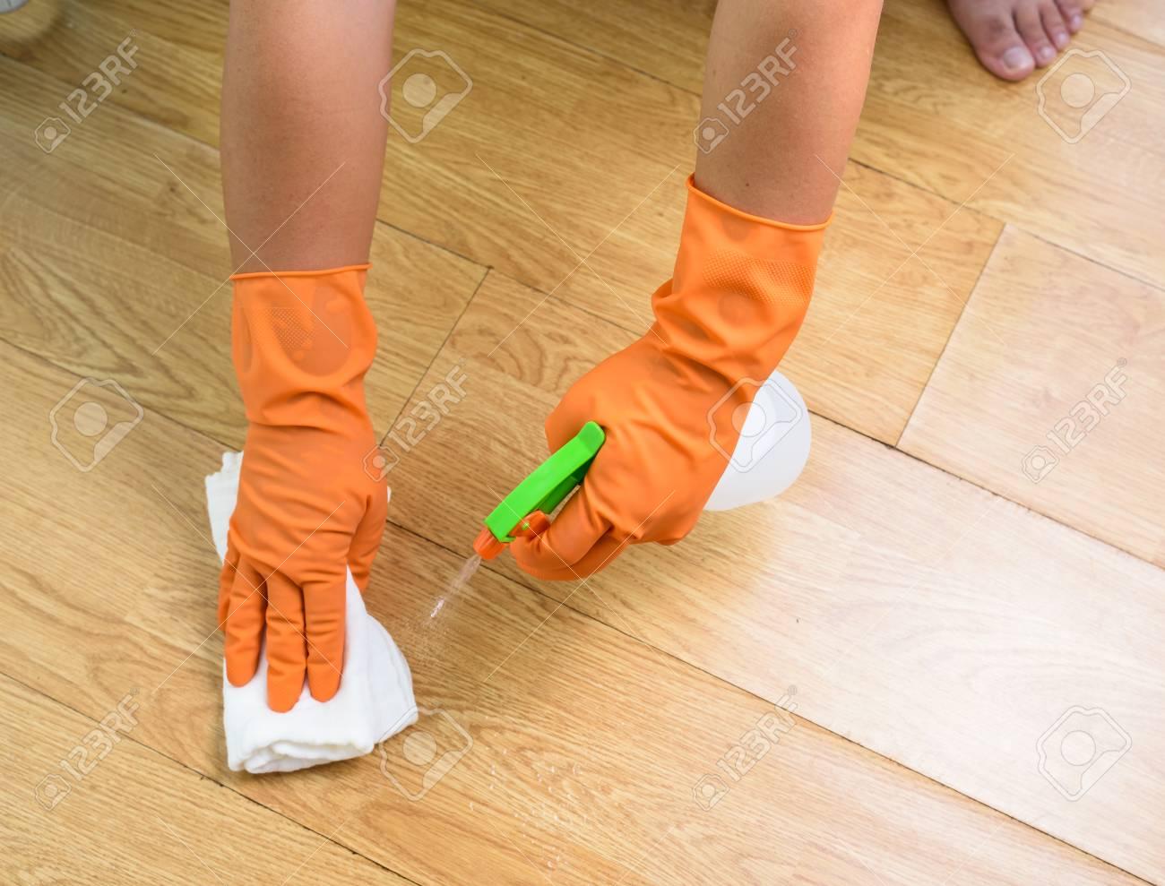 Holzfußboden Reinigen ~ Hand in handschuhe reinigung holzboden mit lappen und reiniger spray