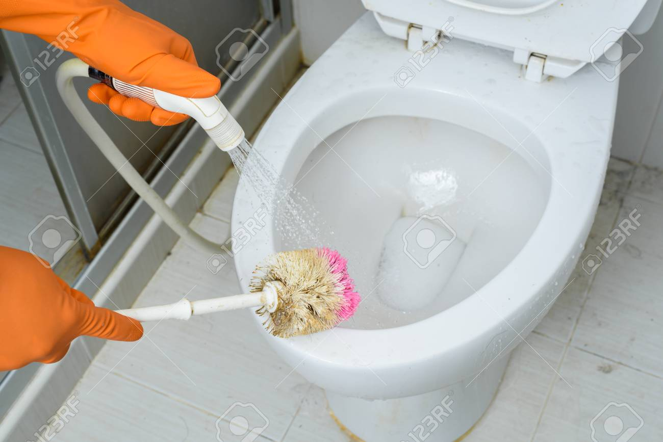 Hands In Orange Gloves Cleaning WC, Toilet, Lavatory Using Brush ...