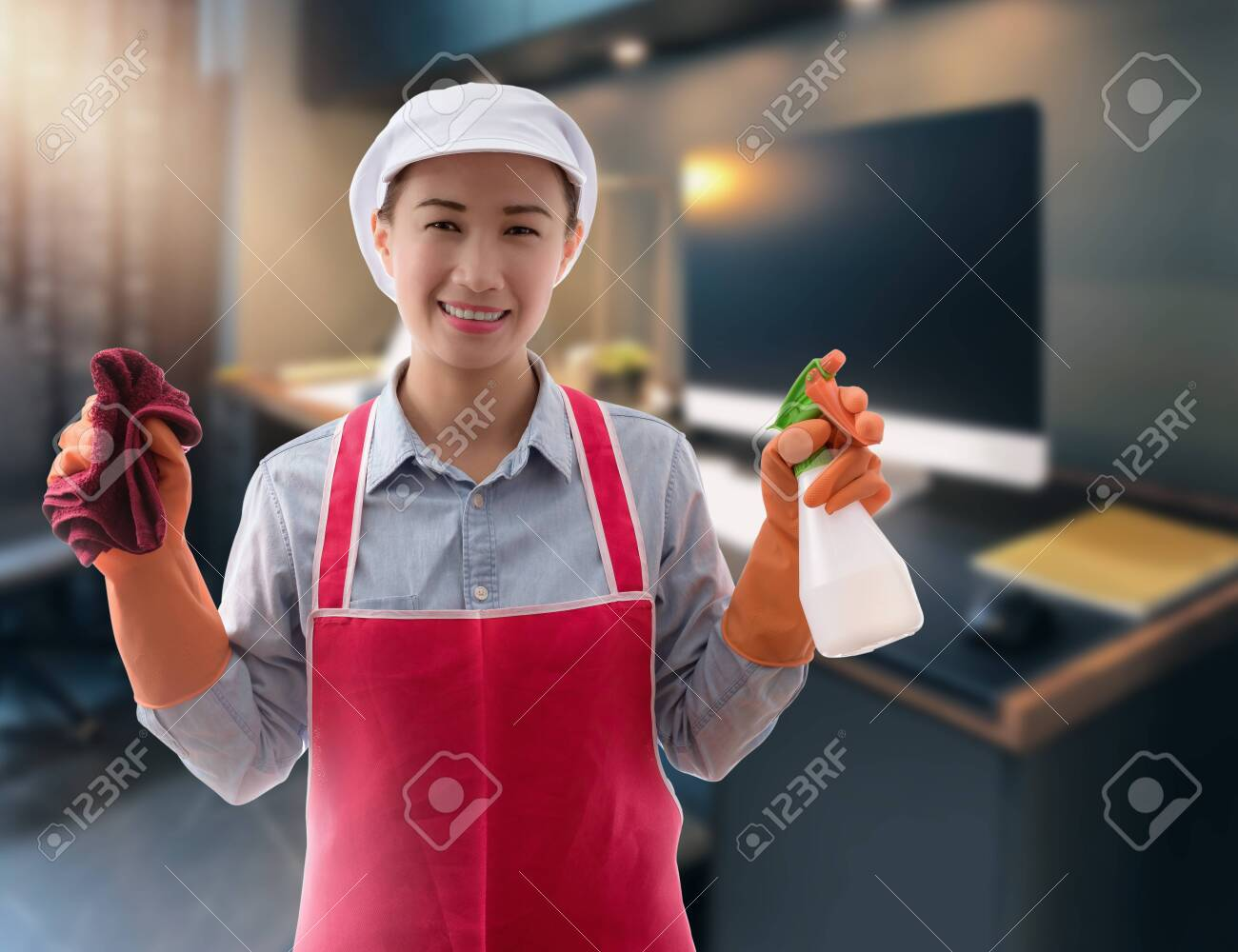 Cleaning concept Woman with bucket of washing fluids and rags in hands and cleaning equipment ready to clean house on blurred workingroom background - 147554605