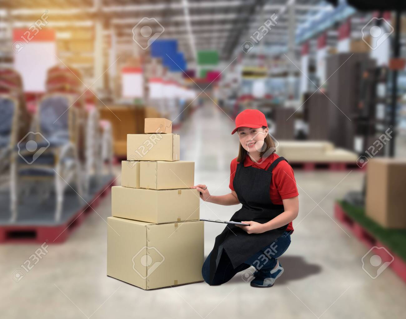 Female staff Delivering products Sign the signature on the product receipt form with parcel boxes Blurred the background of the warehouse - 148081579