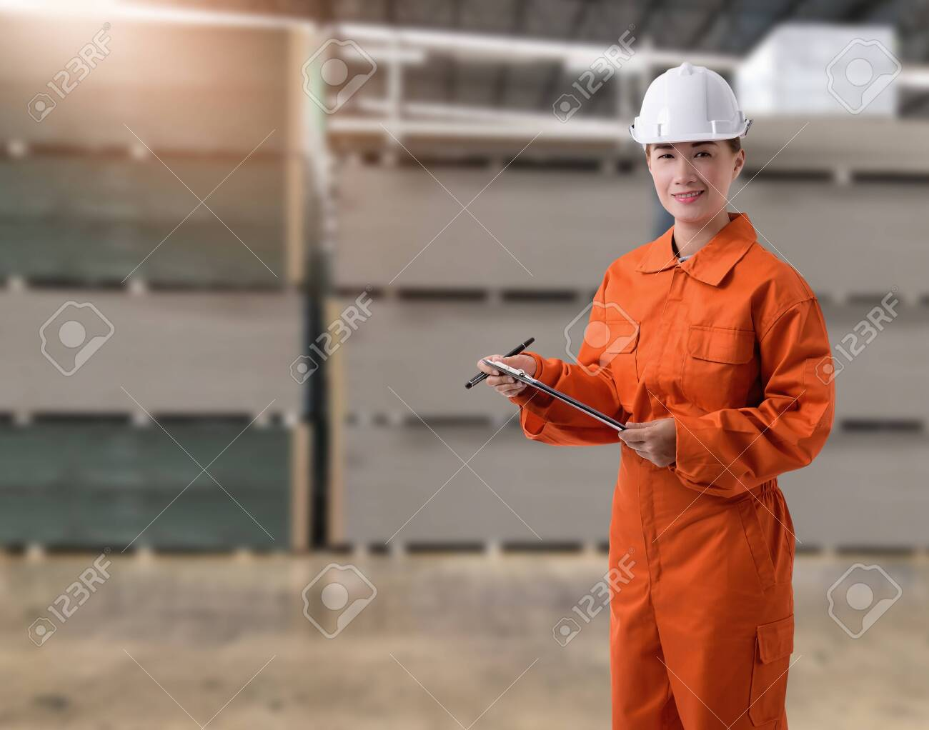 Portrait of Female staff warehouse operator with Blurred the background of Construction material on product shelf in store - 148082217