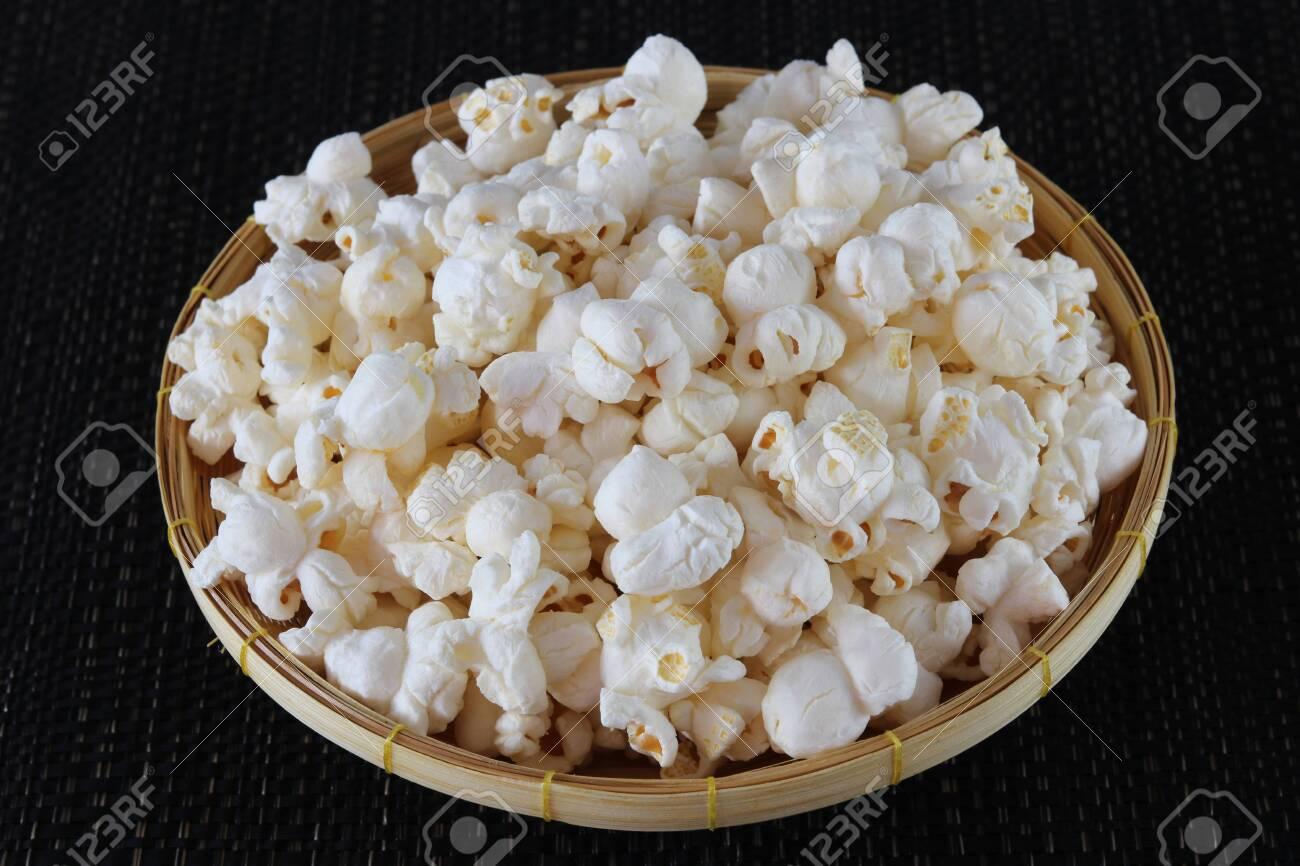 Popcorn in basket on black background close up - 134729924