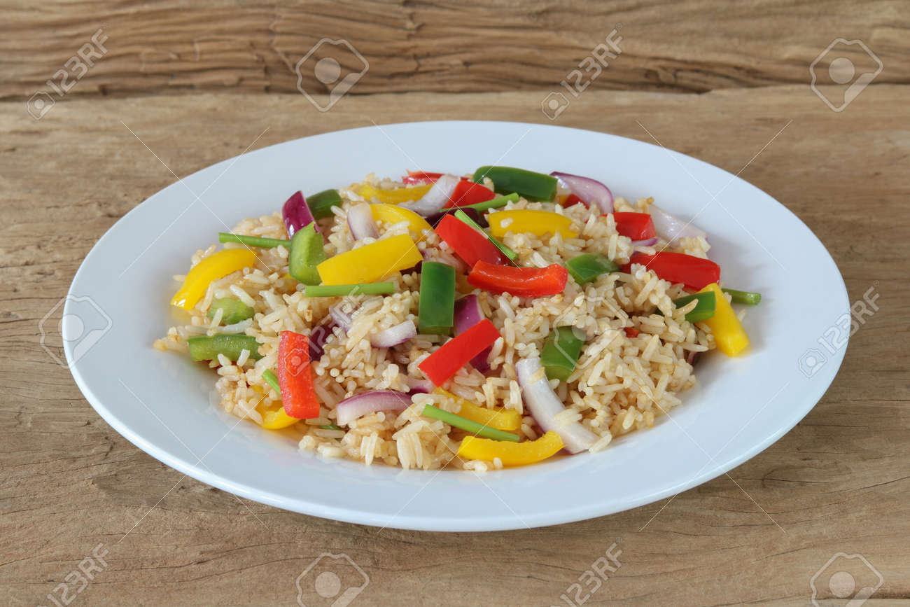 Fried rice with sweet pepper on old wooden background.Homemade meal for good health - 157213342