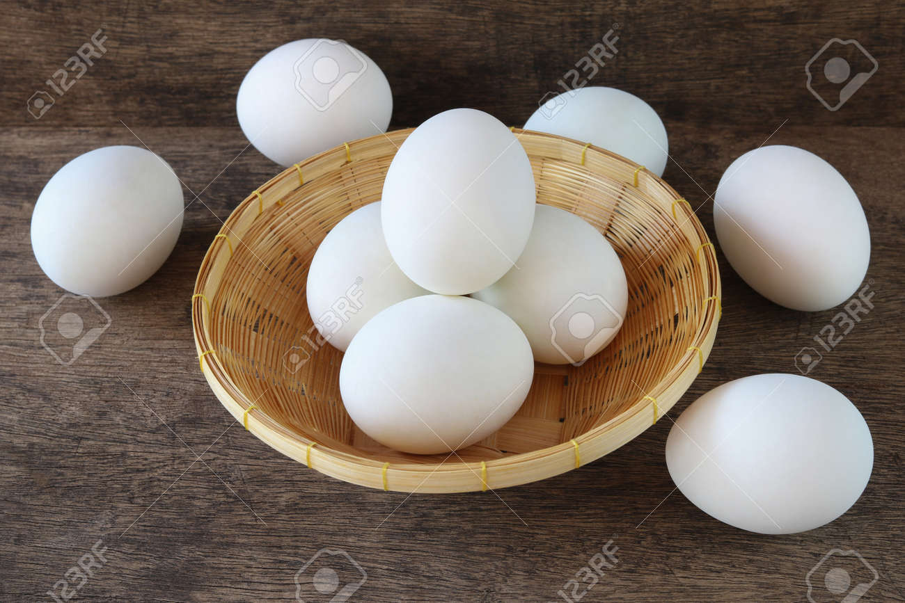 Salted duck eggs in basket on old wooden background - 173008612