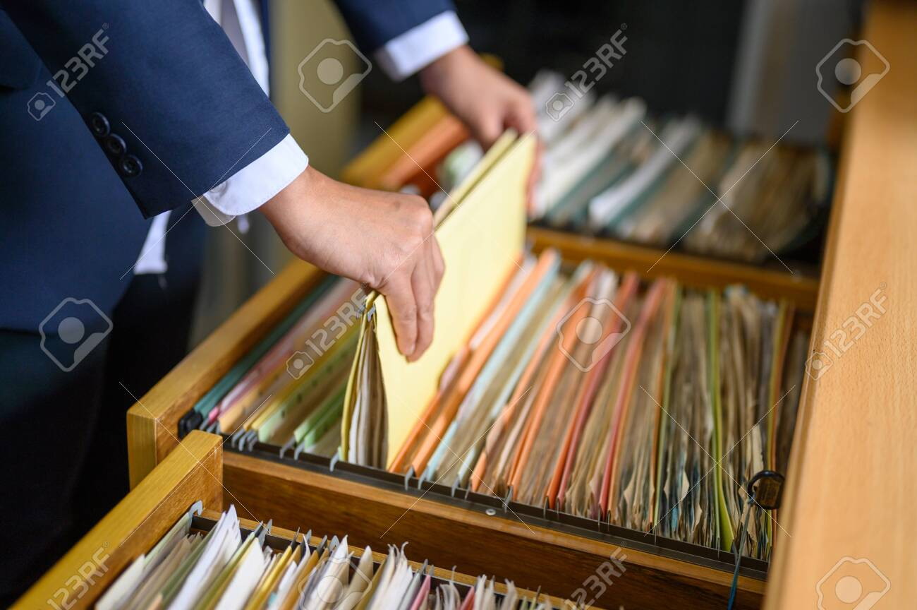 Employees are managing documents at the office. - 126033002