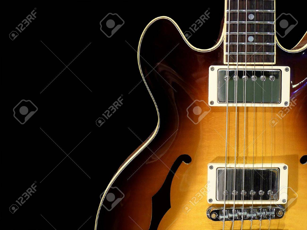 Close Up Of Vintage Electric Jazz Guitar On Black Background Stock
