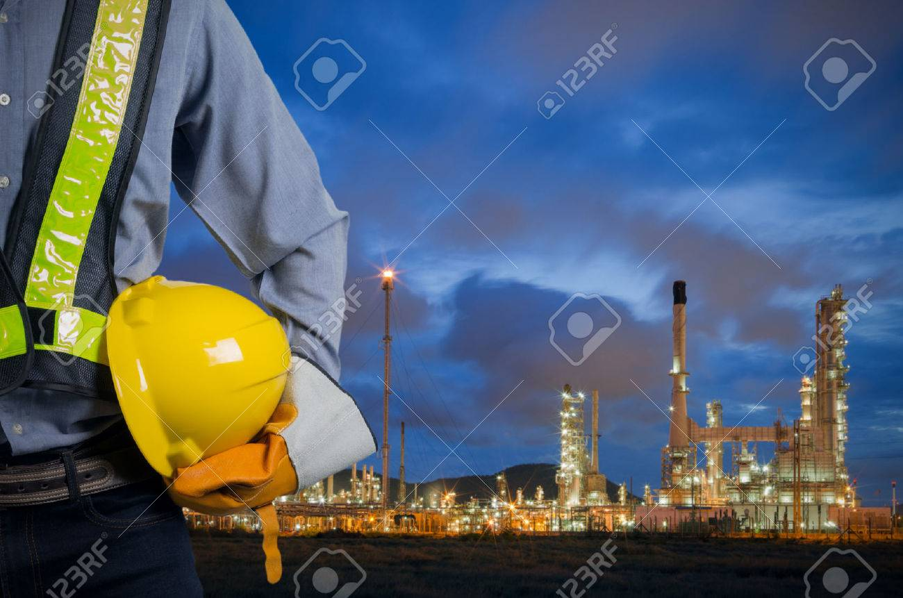 Engineer holding a yellow helmet for the safety of workers on the background oil refinery. Beautiful sky at dawn - 51644295