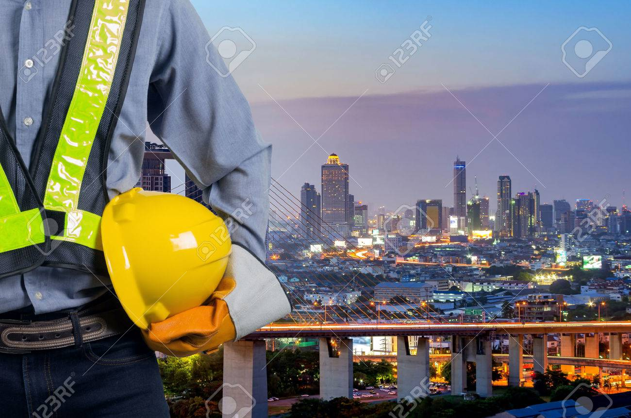 Engineer holding a yellow helmet with a backdrop of the city and industry. - 70902989