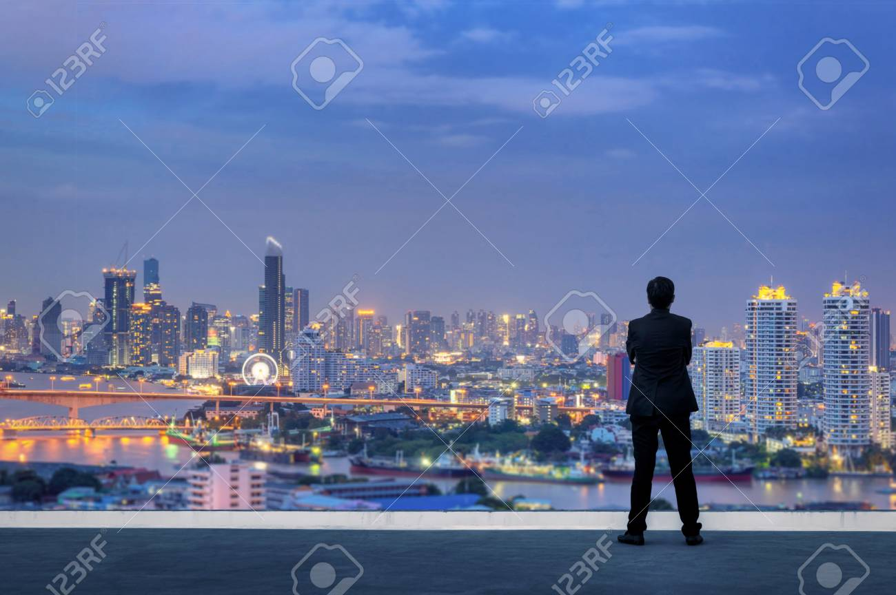Vision concept. Successful businessman standing with hands crossed on chest, On top of building and looking through Cityscape Skyline Night Light. - 100182915