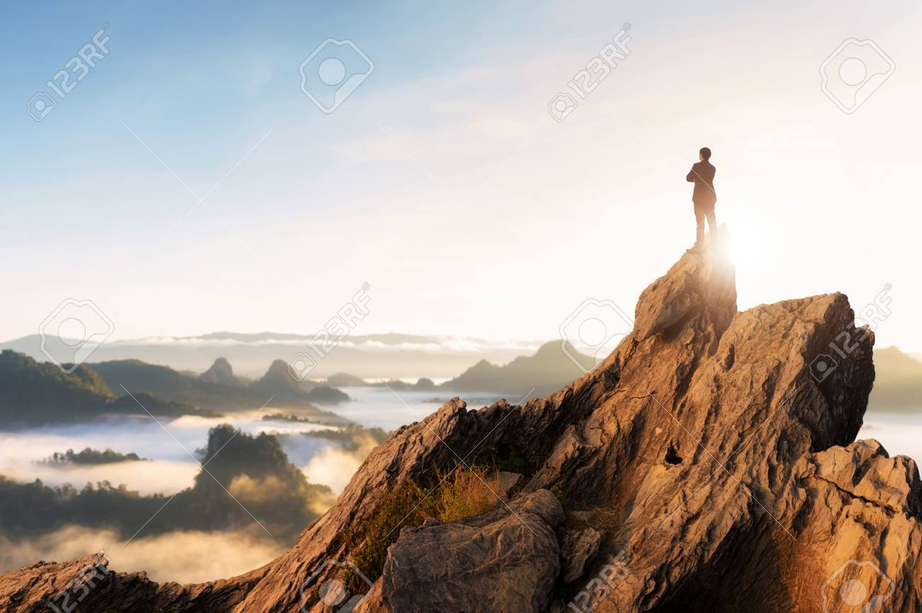 Concept vision, Young businessman wearing comfortable casual suit jacket standing chest hug on top of peak mountain and looking forwards, success, competition and leader concept. - 103119681