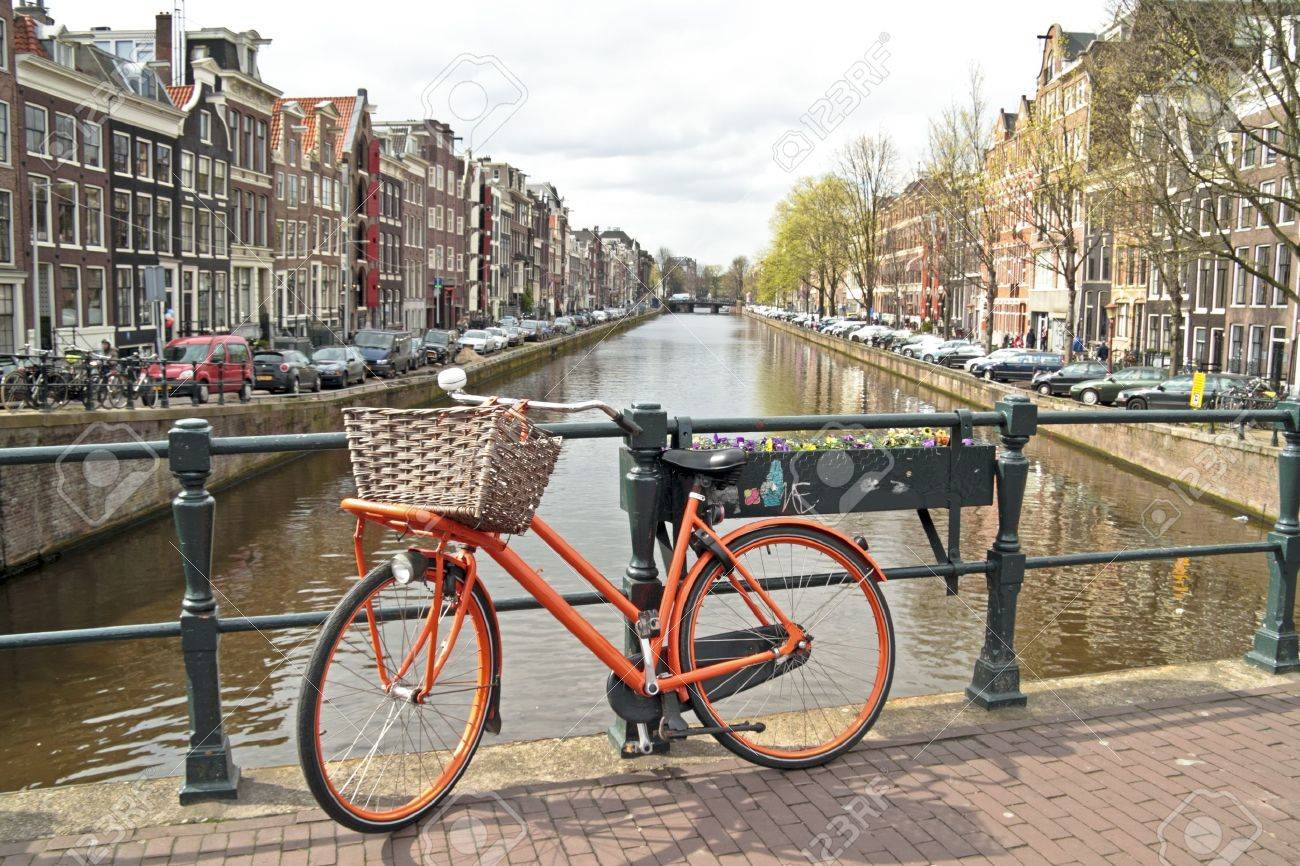 Orange bike on the bridge in Amsterdam city in the Netherlands Stock Photo - 14607193