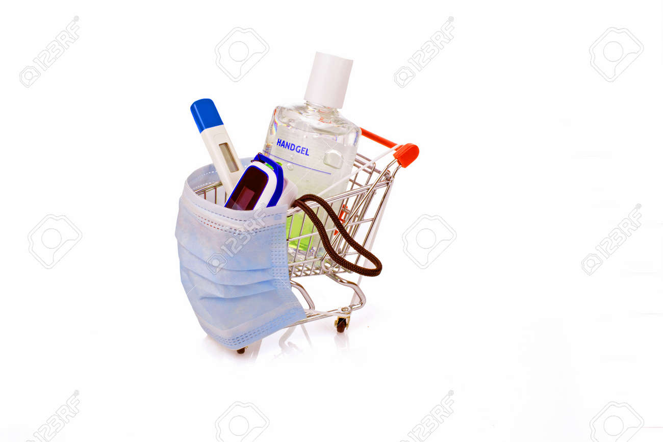 Desinfentant gel, thermometer, blood saturation meter and a medical mask in a shopping cart, concept - 172325093
