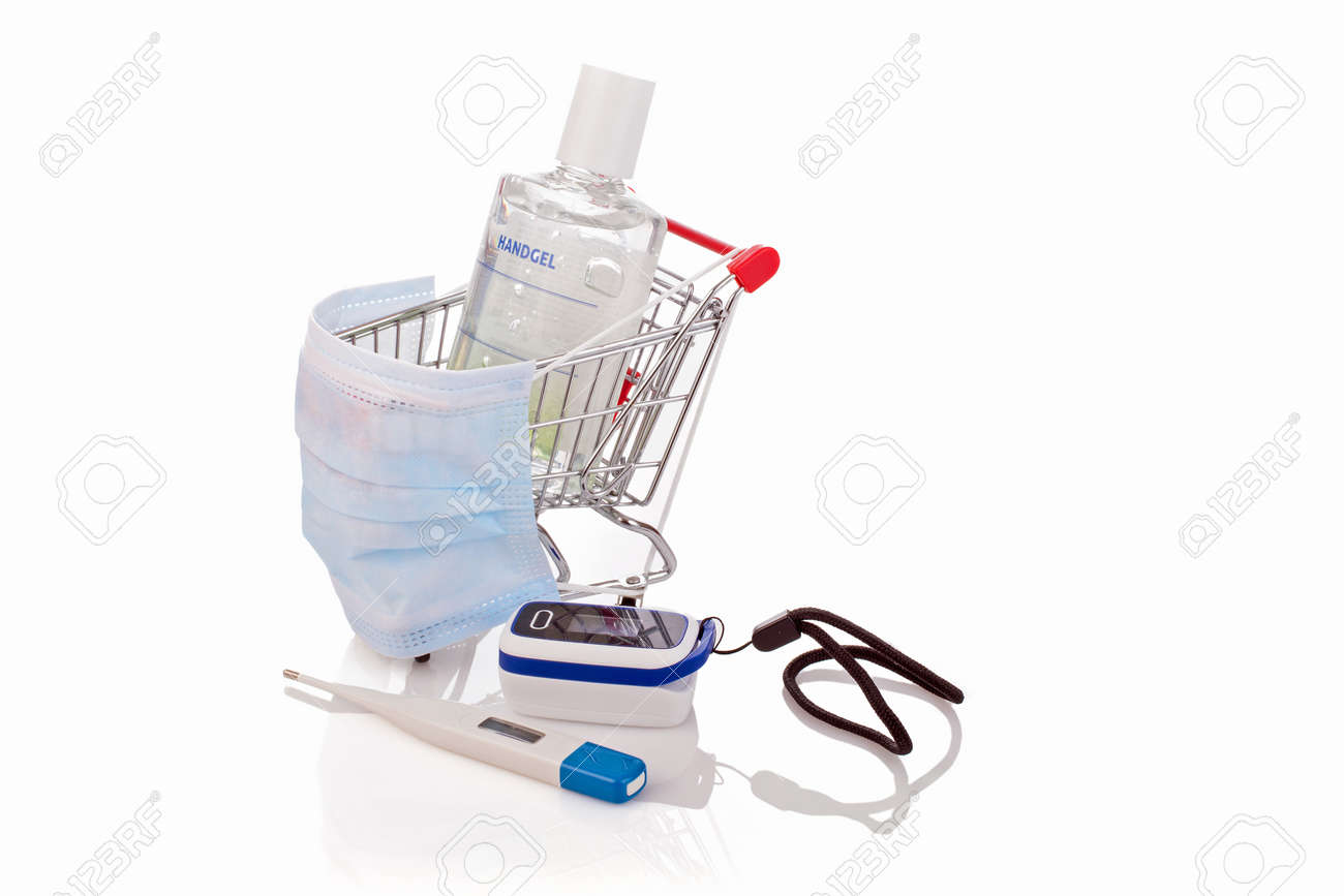 Desinfentant gel, thermometer, blood saturation meter and a medical mask in a shopping cart, concept - 172325278