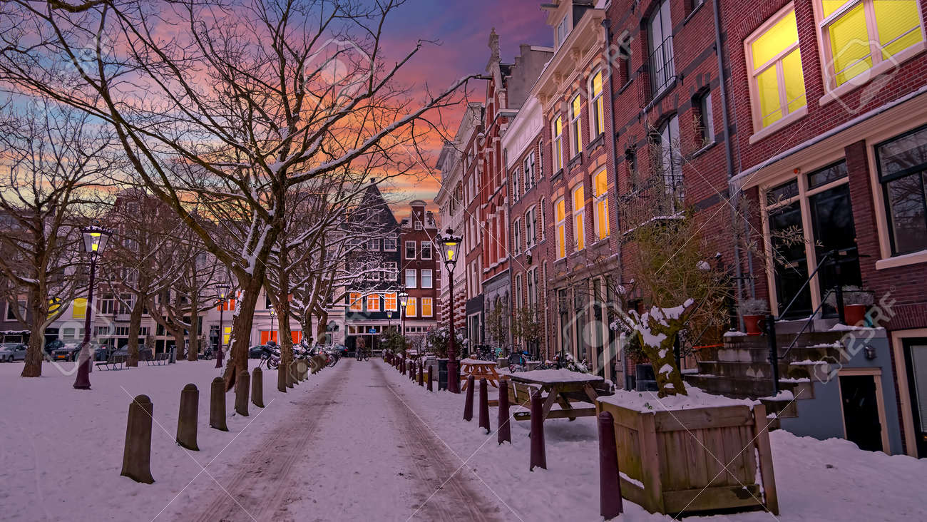 City scenic from a snowy Amsterdm in winter in the Netherlands at sunset - 173297773