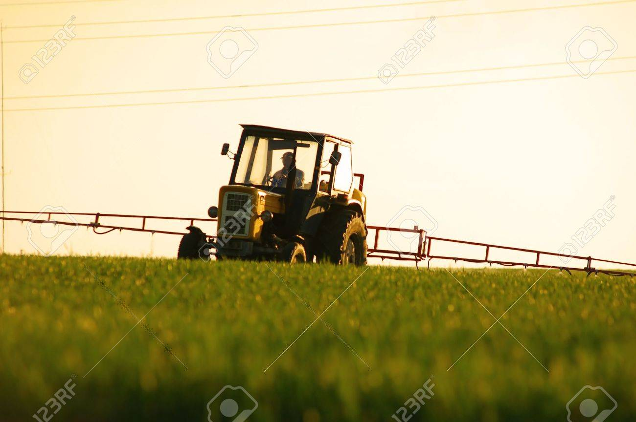 Spraying the Crop. Focus on tractor Stock Photo - 1105567