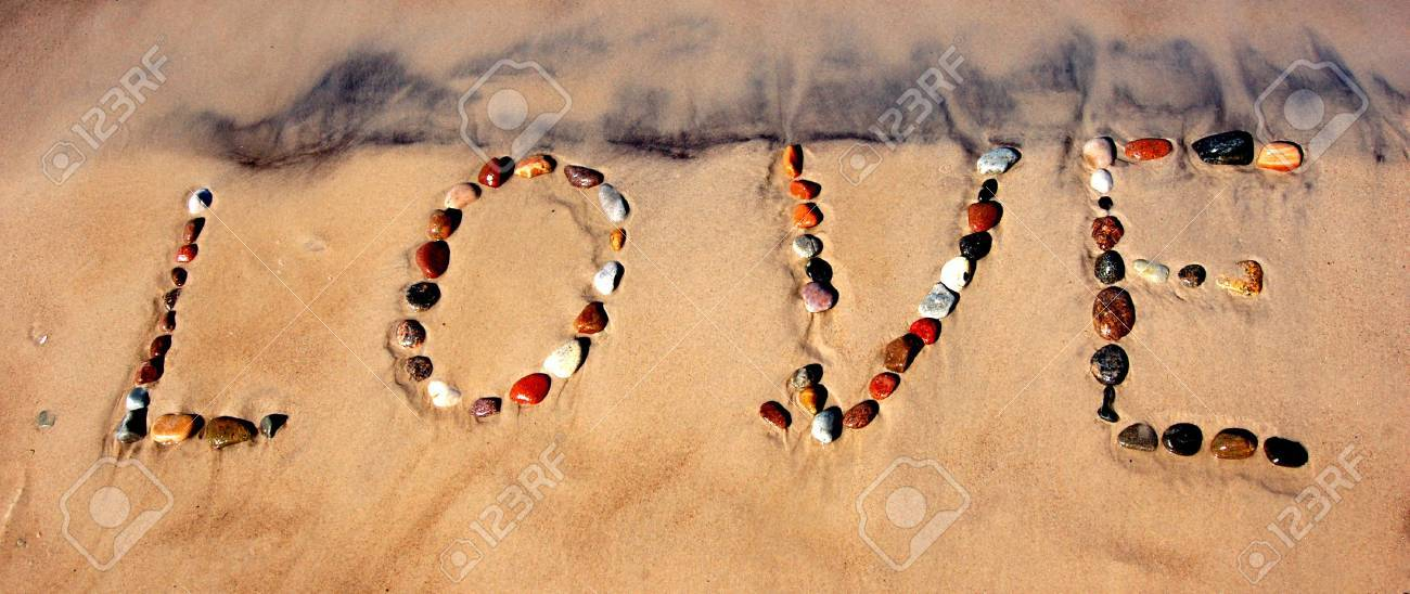 Word LOVE on beach sand, made from rocks Stock Photo - 1133598