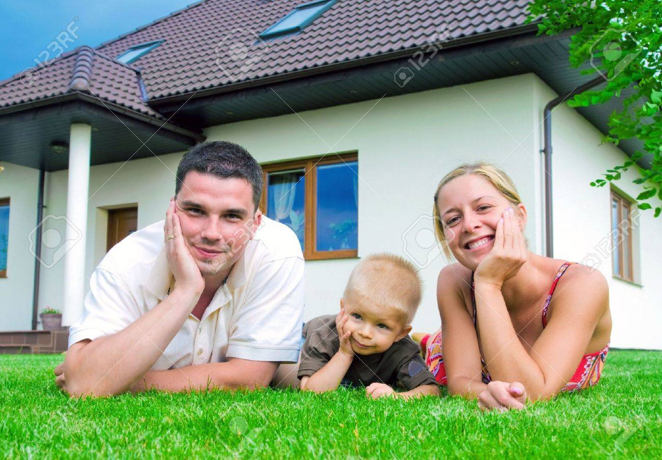 Happy family in front of their house - 5340195