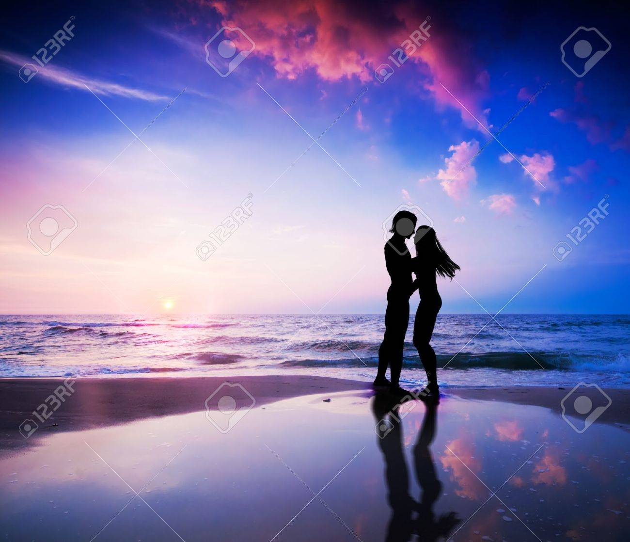 Romantic couple about to kiss on beach at sunset - 12504732