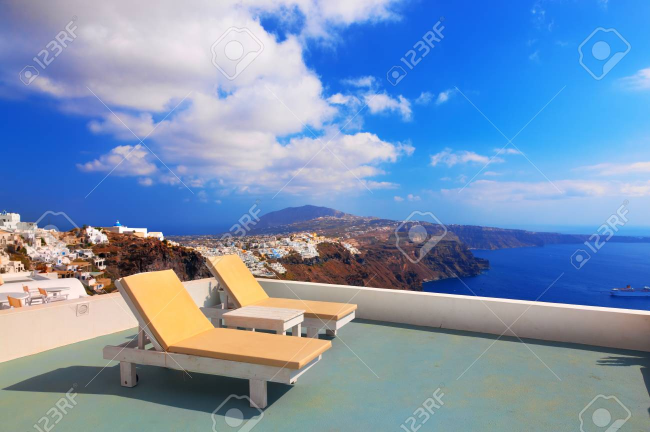 Two deckchairs on the roof of the building on Santorini island,