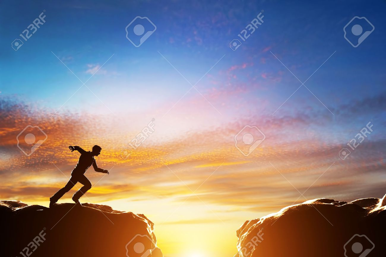 Man running fast to jump over precipice between two mountains. Concepts of determination, business, challenge, success, risk etc. - 34388974