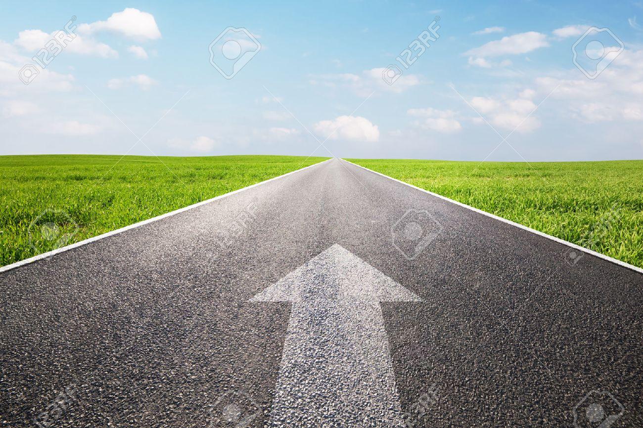 長い空の直線道路で前方を指す矢...