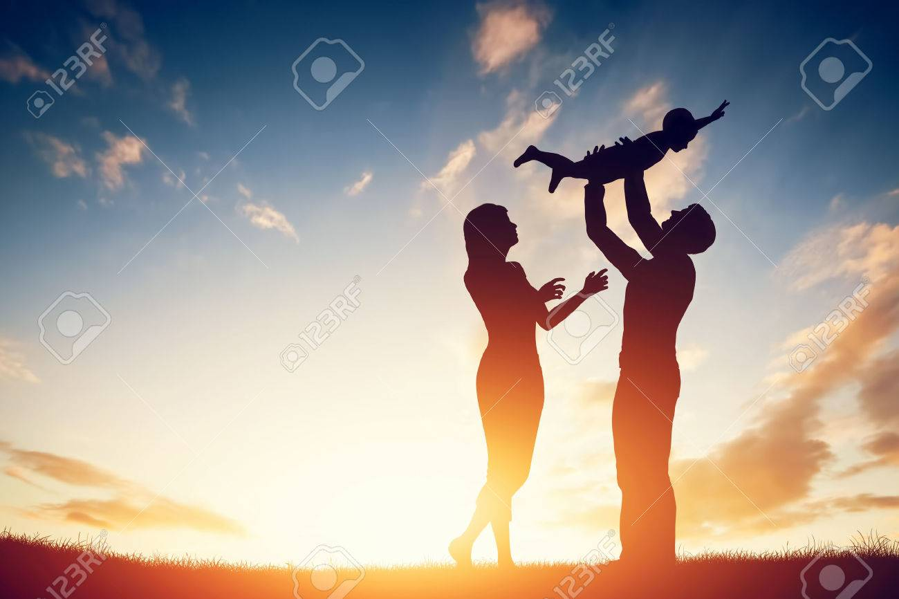 Happy family together, parents with their little child at sunset. Father raising baby up in the air. - 38961503