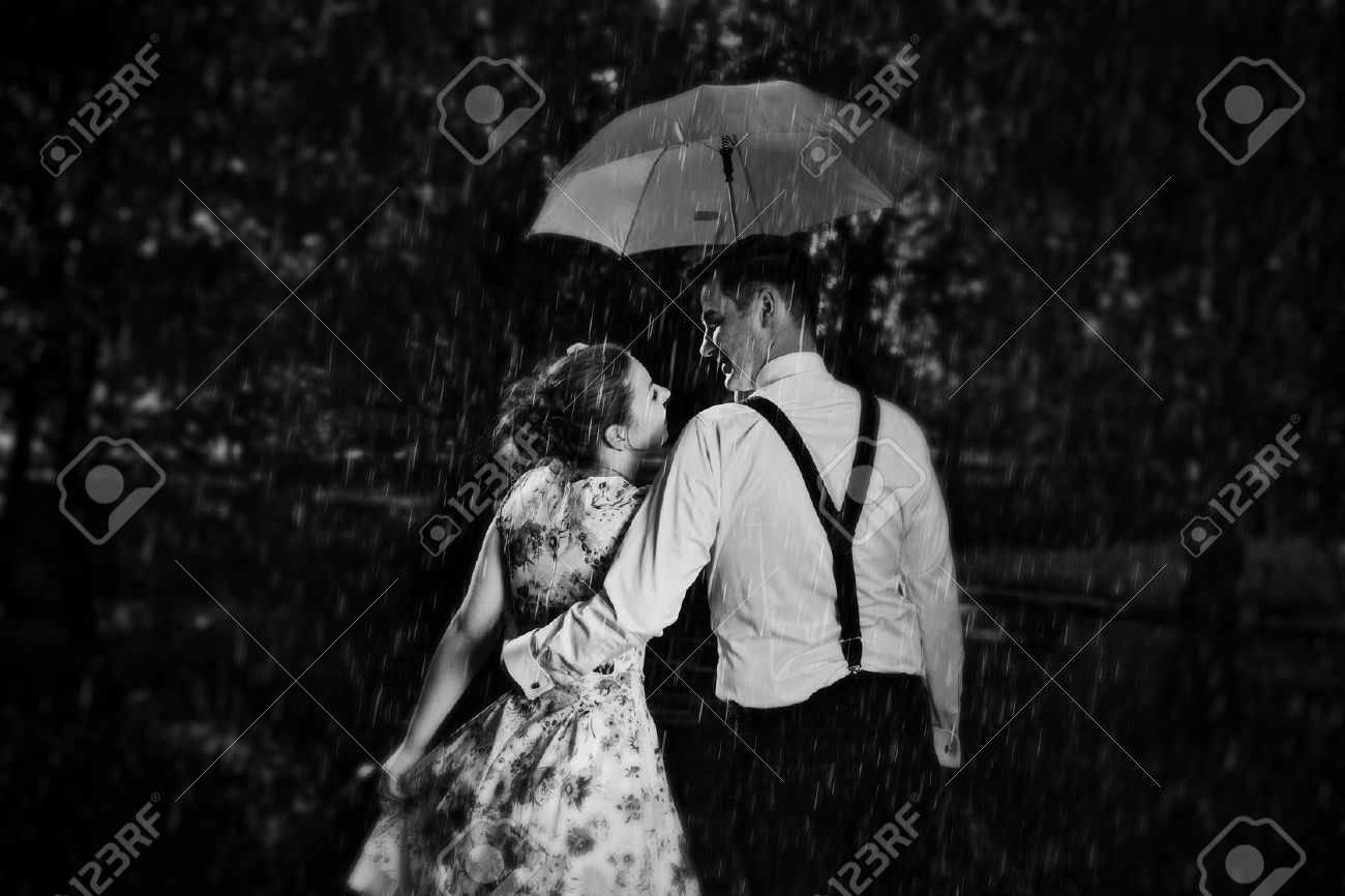 Stock photo young romantic couple in love flirting in rain man holding umbrella dating romance black and white
