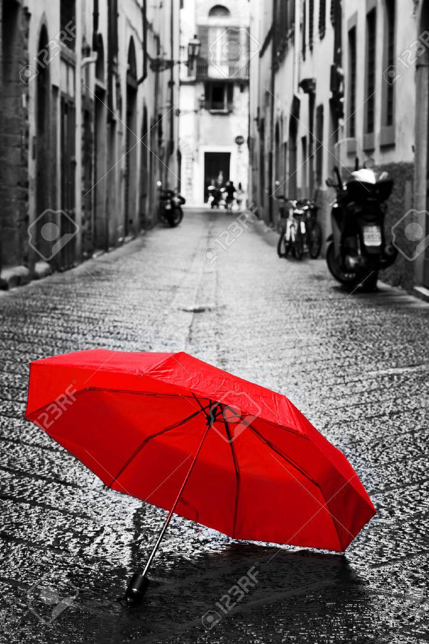 Red umbrella on cobblestone street in the old town wind rain stormy weather