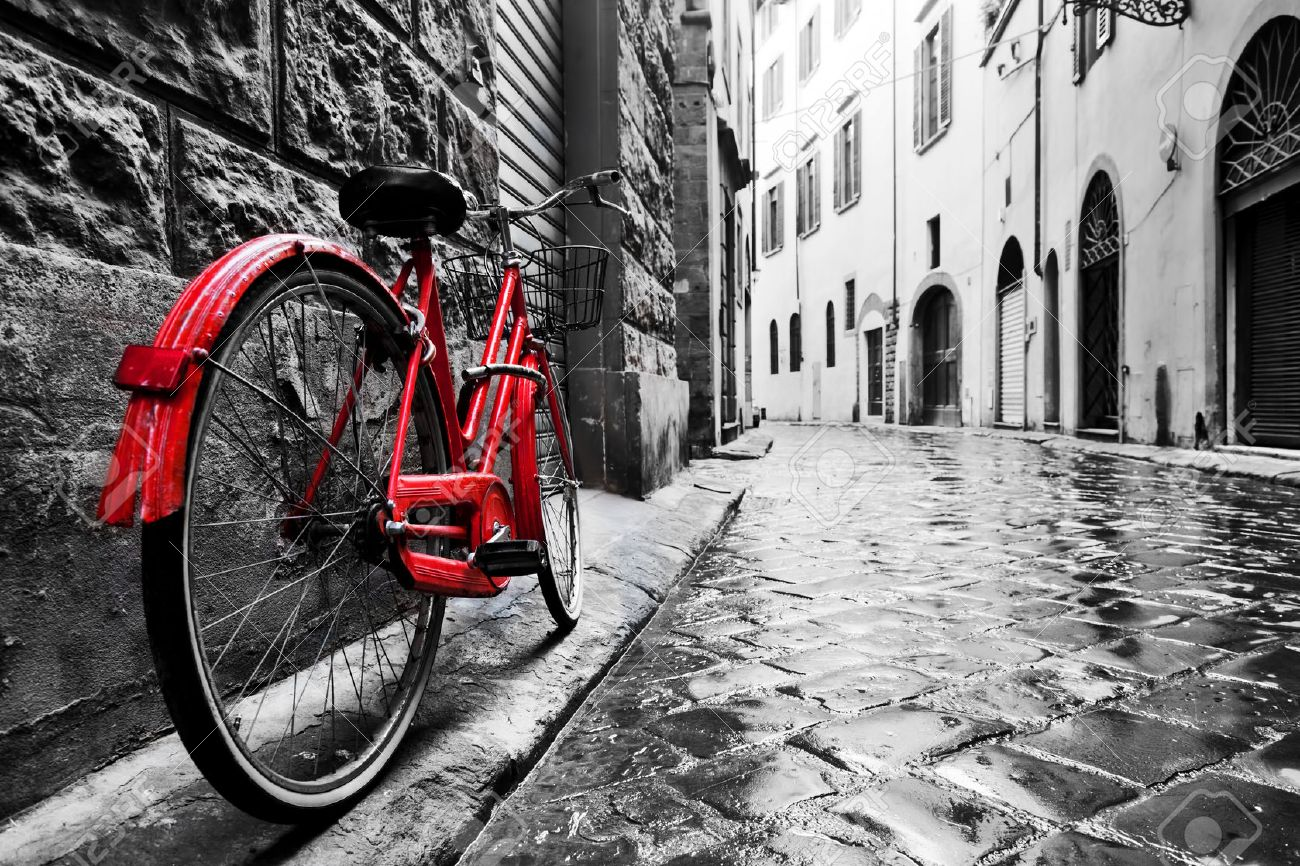 Retro vintage red bike on cobblestone street in the old town. Color in black and white. Old charming bicycle concept. Stock Photo - 50351468