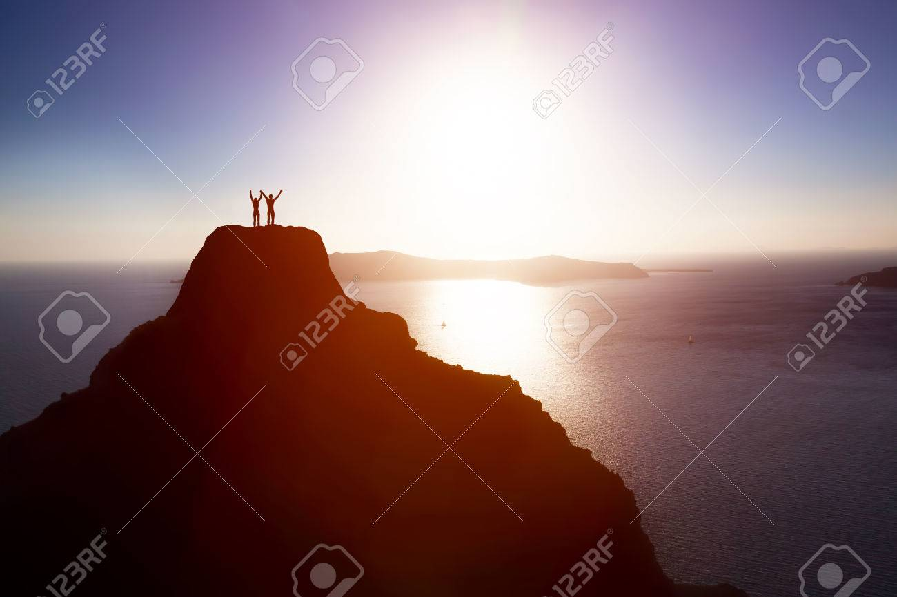 Happy couple on the top of the mountain over ocean celebrating life, success. Concepts of winning together, achieving aim, positive energy. Stock Photo - 50832206