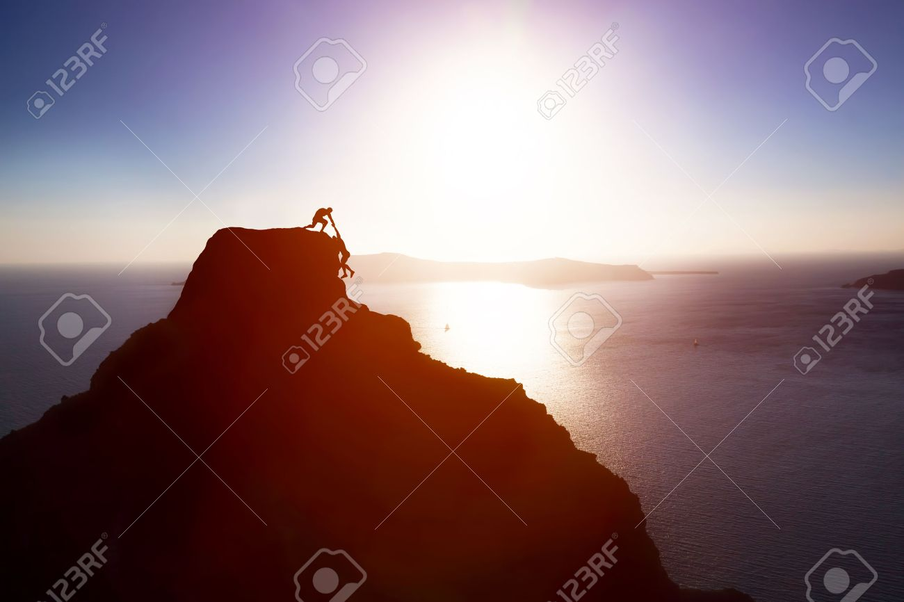 Climber giving hand and helping his friend to reach the top of the mountain. Help, support, assistance, teamwork in a dangerous situation concepts Stock Photo - 50832217