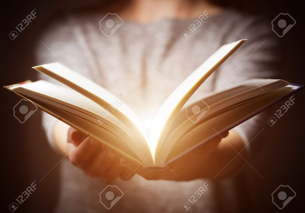 Light coming from book in woman's hands in gesture of giving, offering. Concept of wisdom, religion, reading, imagination. Stock Photo - 50832678
