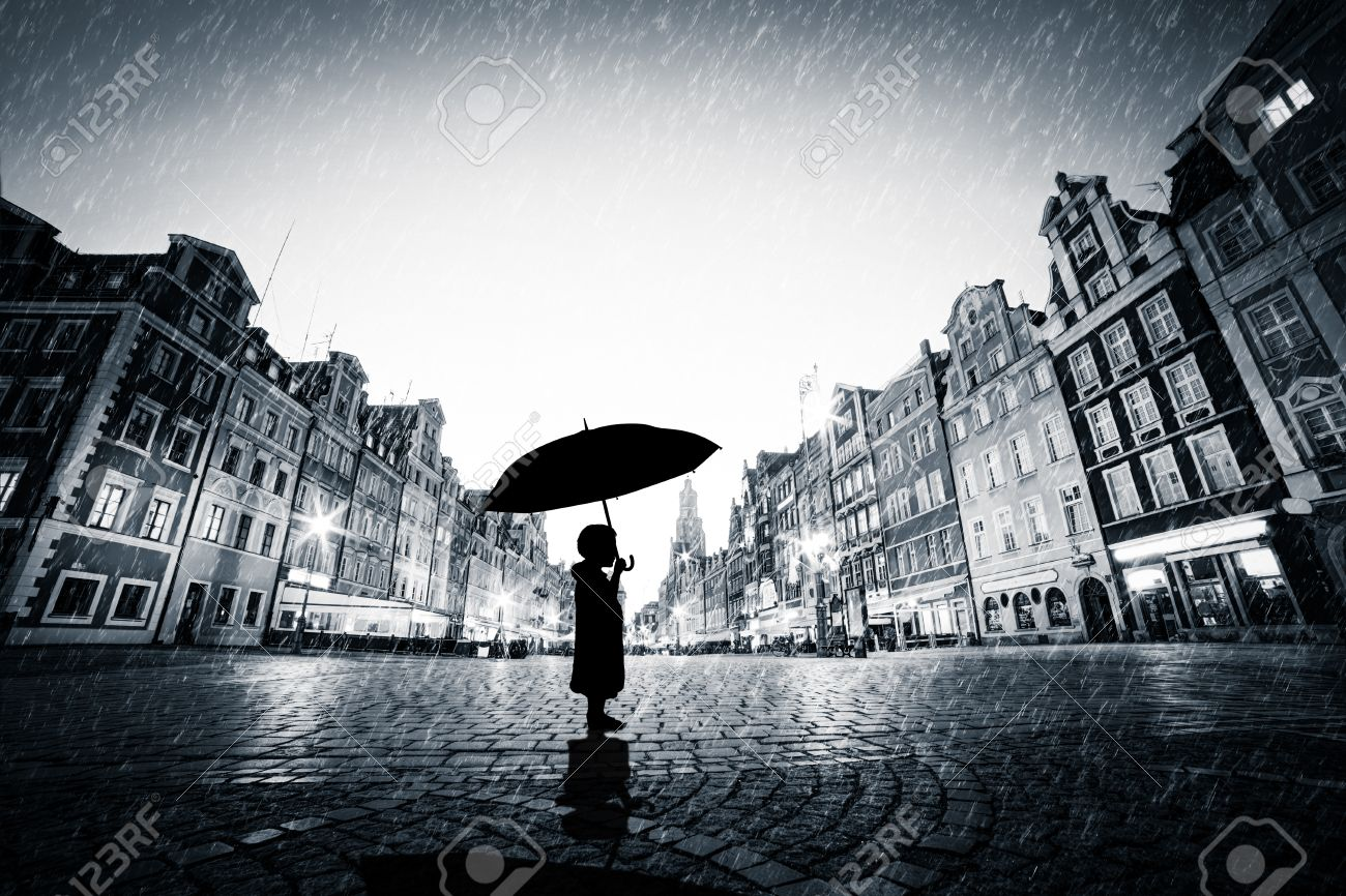Child with umbrella standing alone on cobblestone old town in rain. Concept of being lost, lonely in a big world or exploring Stock Photo - 50837478