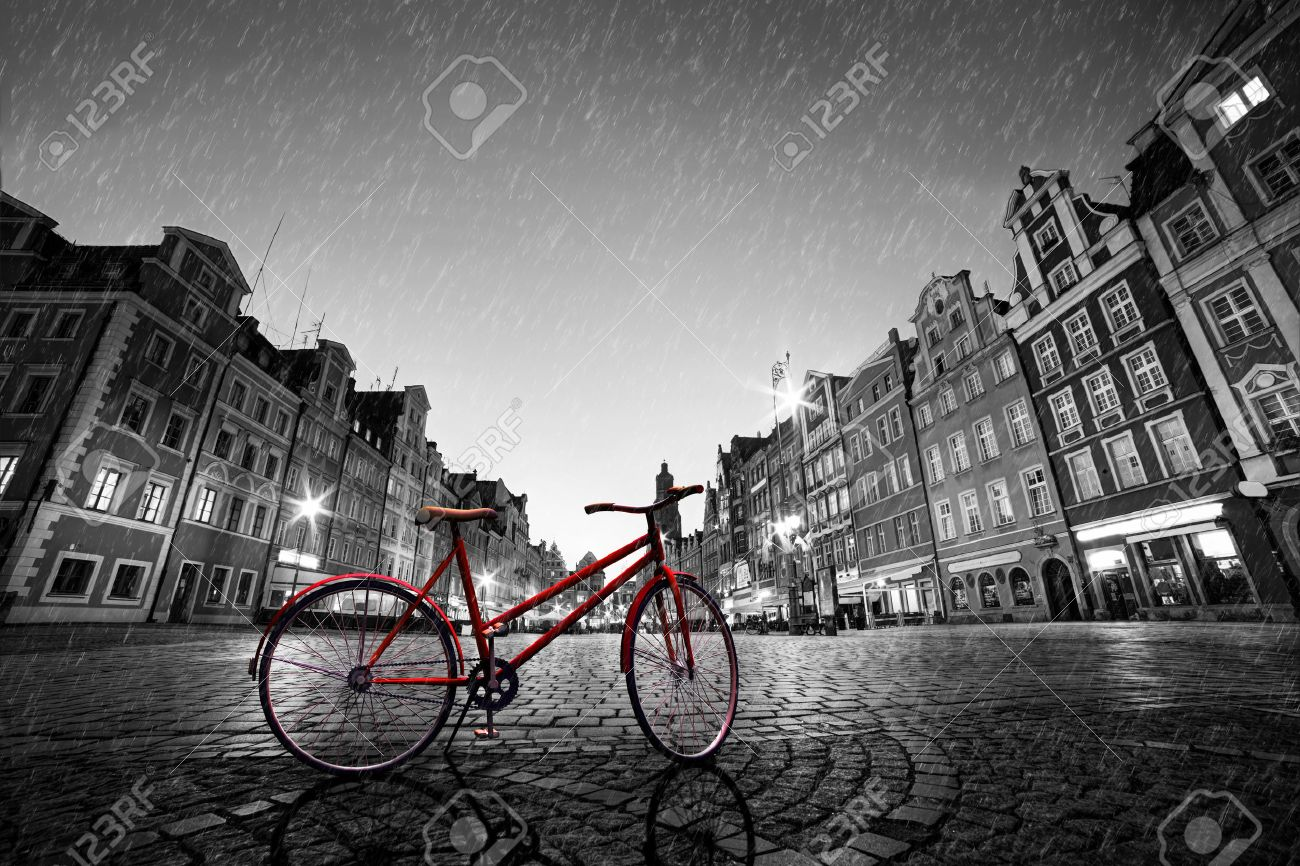 Vintage red bike on cobblestone historic old town in rain color