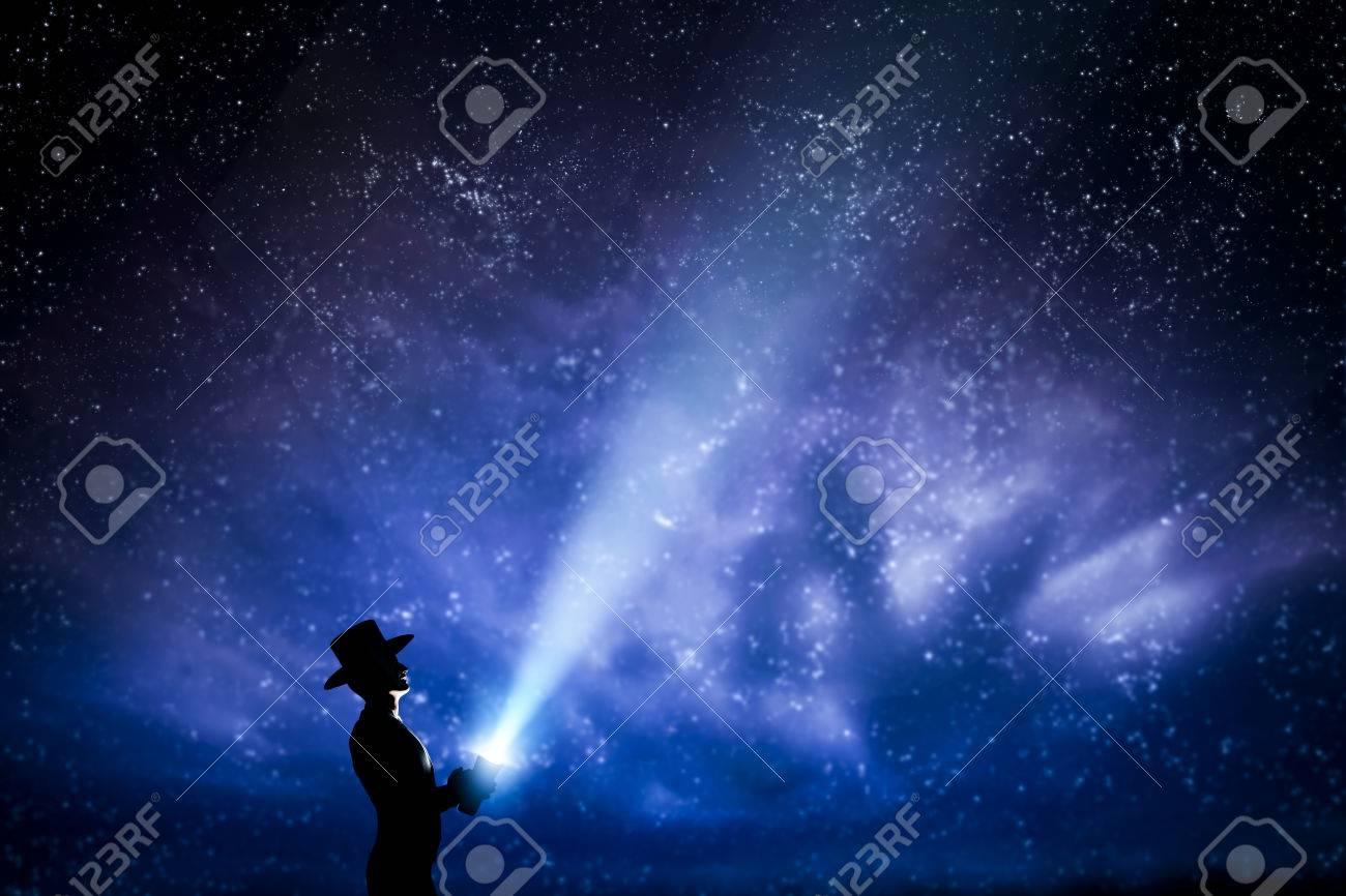 Man in hat throwing light beam up the night sky full of stars. Conceptual - explore, dream, magic, fantasy. Standard-Bild - 54942291