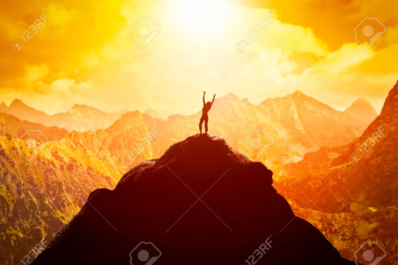 Happy woman with hands up on the peak of the mountain enjoying the success, freedom and bright future. Stock Photo - 54941501