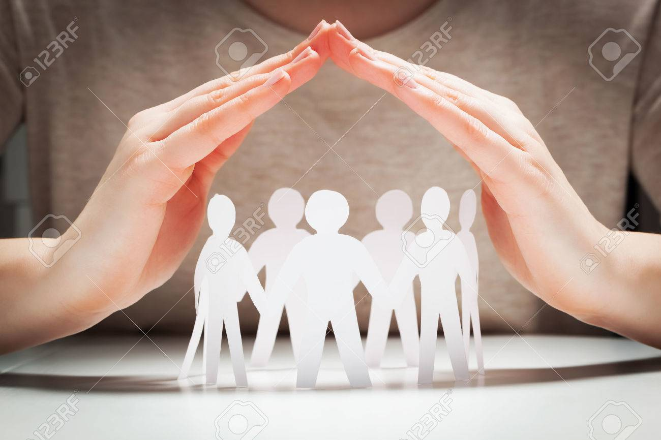 Paper people under hands in gesture of protection. Concept of insurance, social protection and support. Stock Photo - 56766663