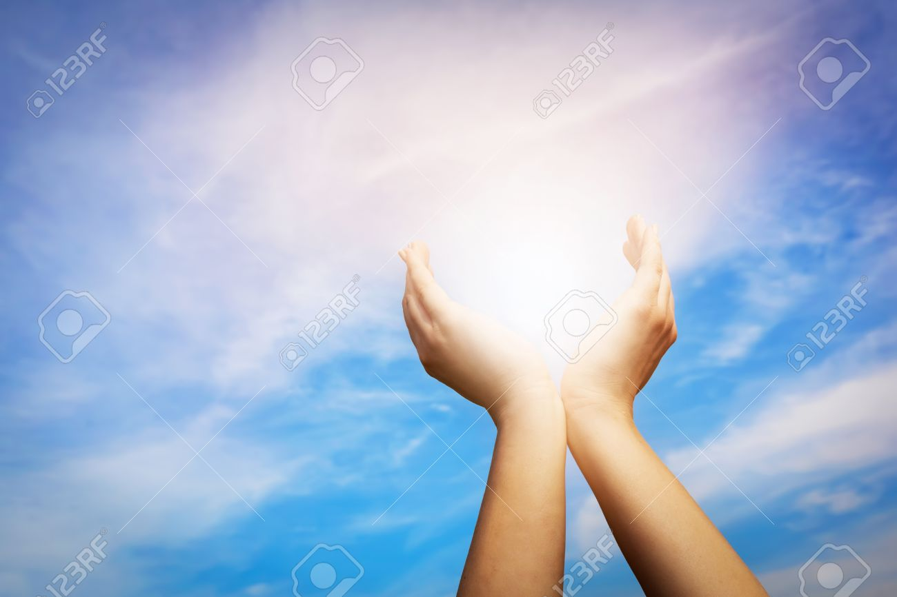 Raised hands catching sun on blue sky. Concept of spirituality, wellbeing, positive energy etc. Standard-Bild - 61712964