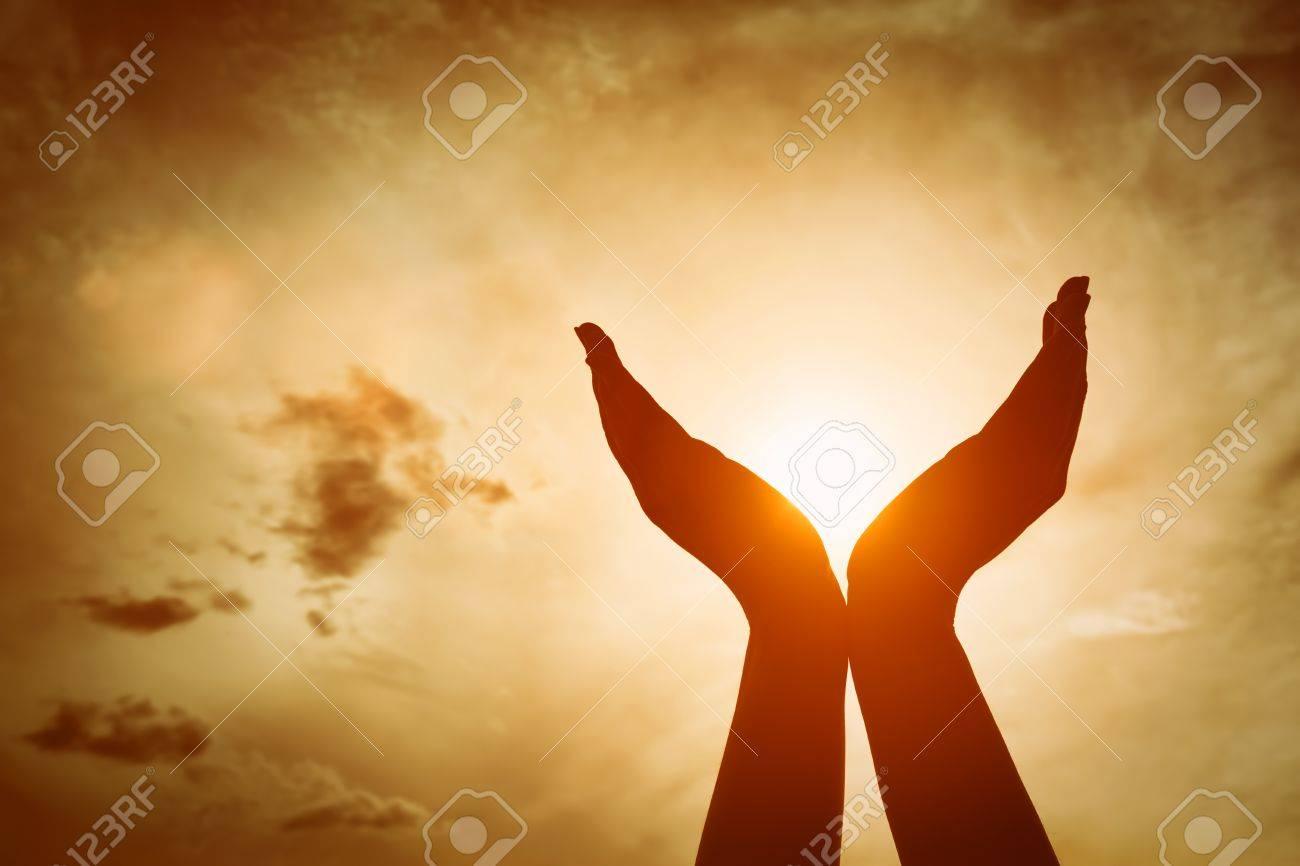Raised hands catching sun on sunset sky. Concept of spirituality, wellbeing, positive energy etc. Standard-Bild - 61712972