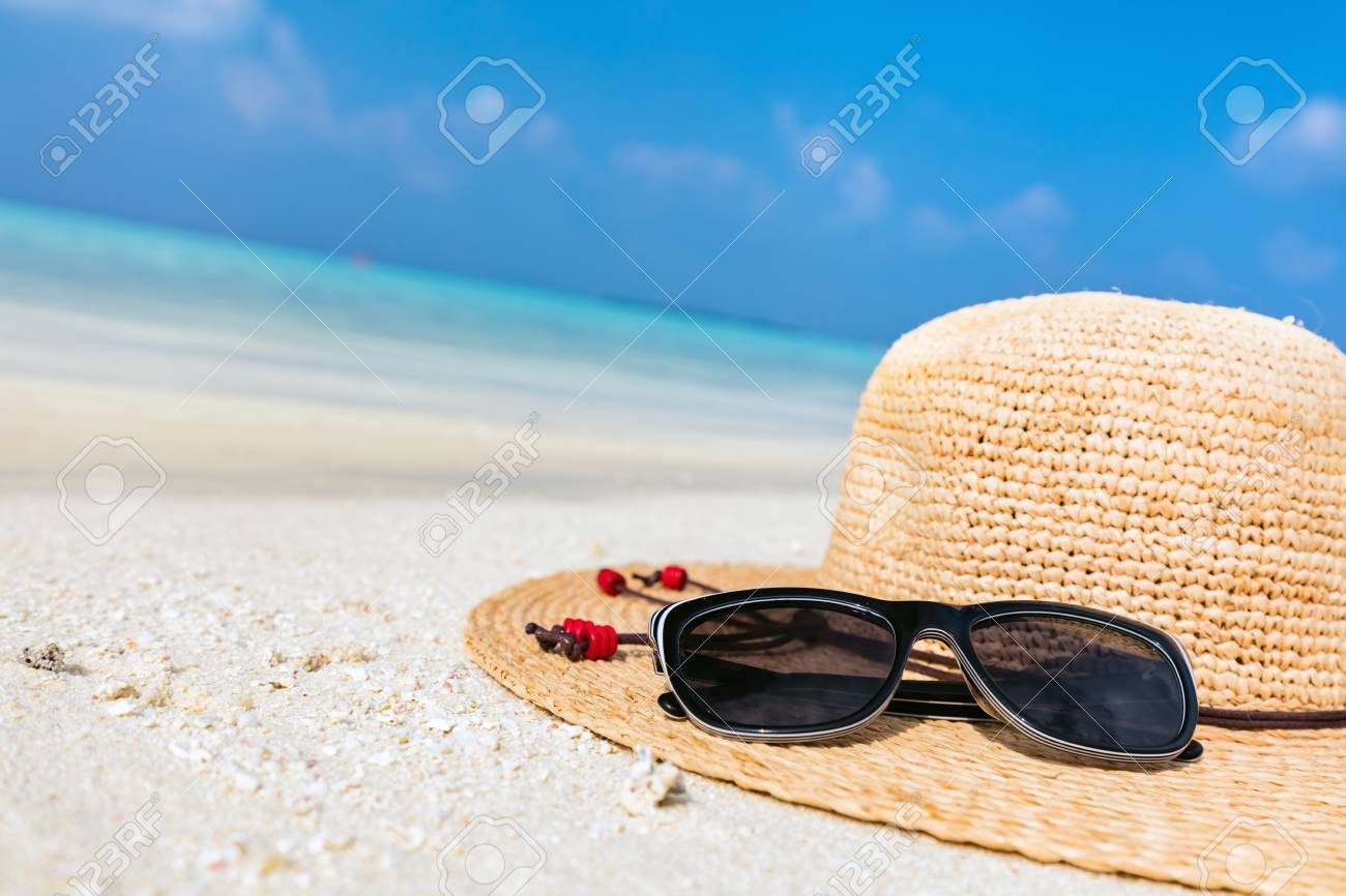 3df13918505 Stock Photo - Sun hat and sunglasses on sand