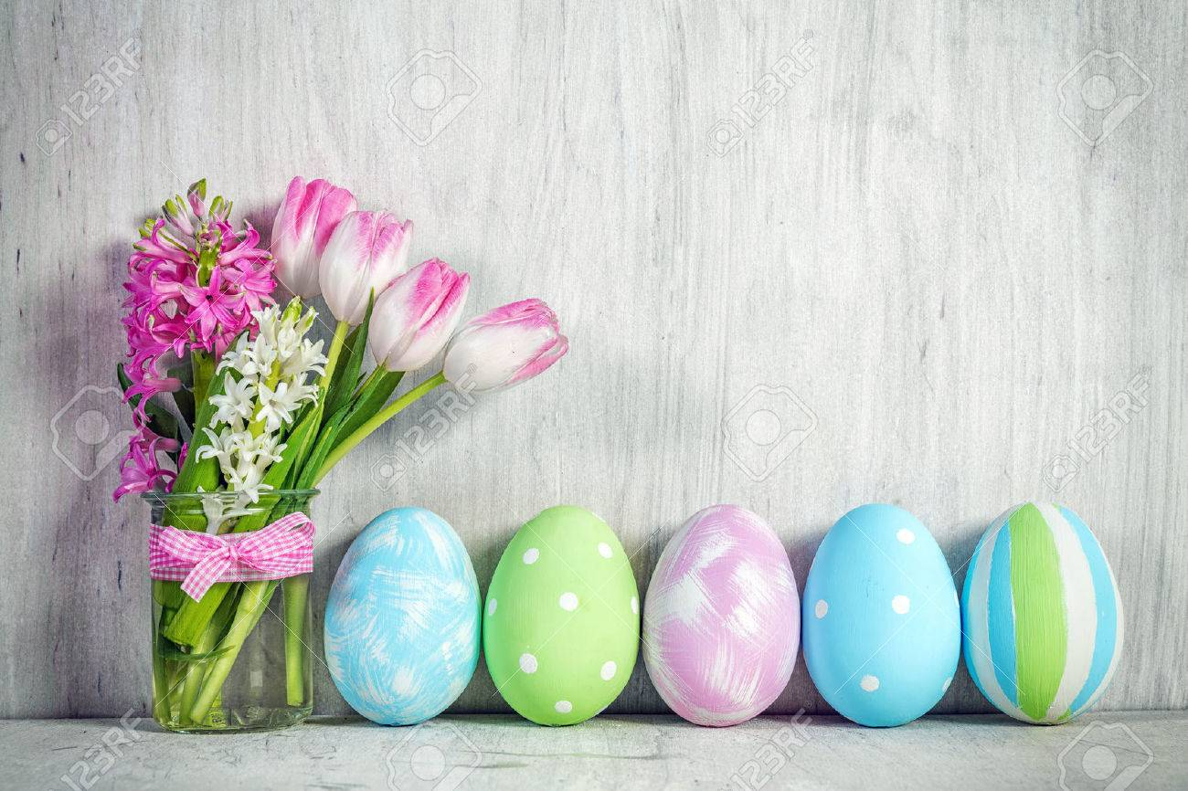 Easter eggs and a spring bouquet of tulips on a wooden table. Springtime decoration. Standard-Bild - 73006093