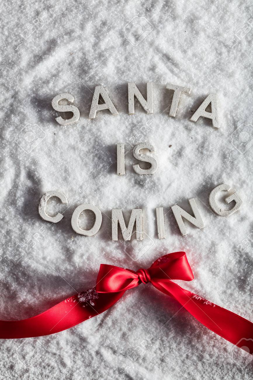 SANTA IS COMING Writing And A Red Bow On Snowy Background. Christmas ...