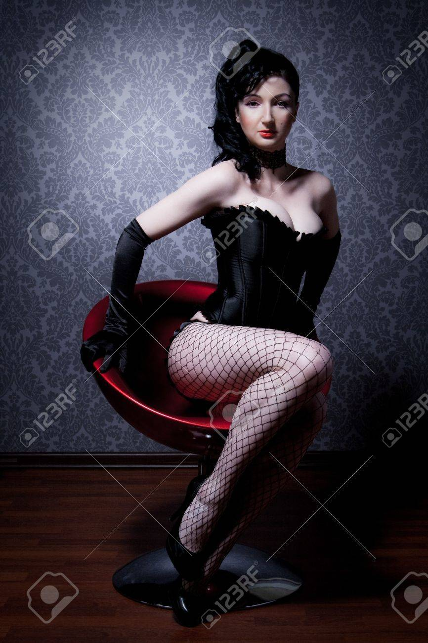Attractive young woman in a corset is sitting on a chair and looks into the camera Stock Photo - 9457019