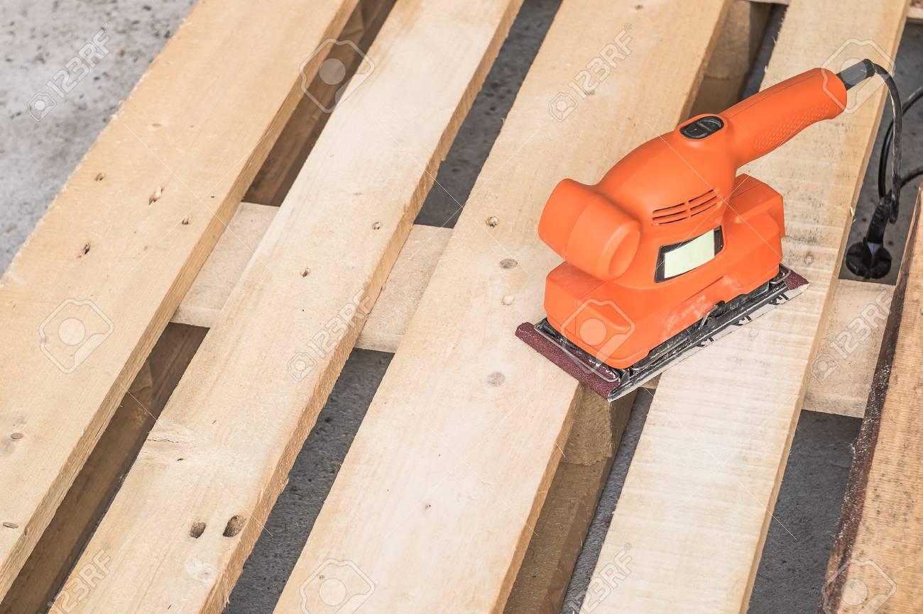 Ponceuse Pour Poutre Bois ponceuses à bois, menuisier travaillant avec une ponceuse électrique sur le  plancher de pin ou la surface de la table