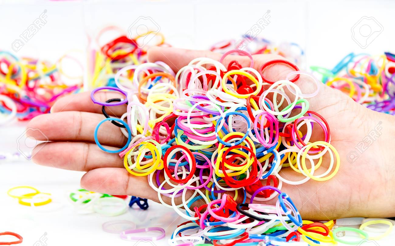 Hands And Pile Of Small Round Colorful Rubber Bands Rainbow Color ...