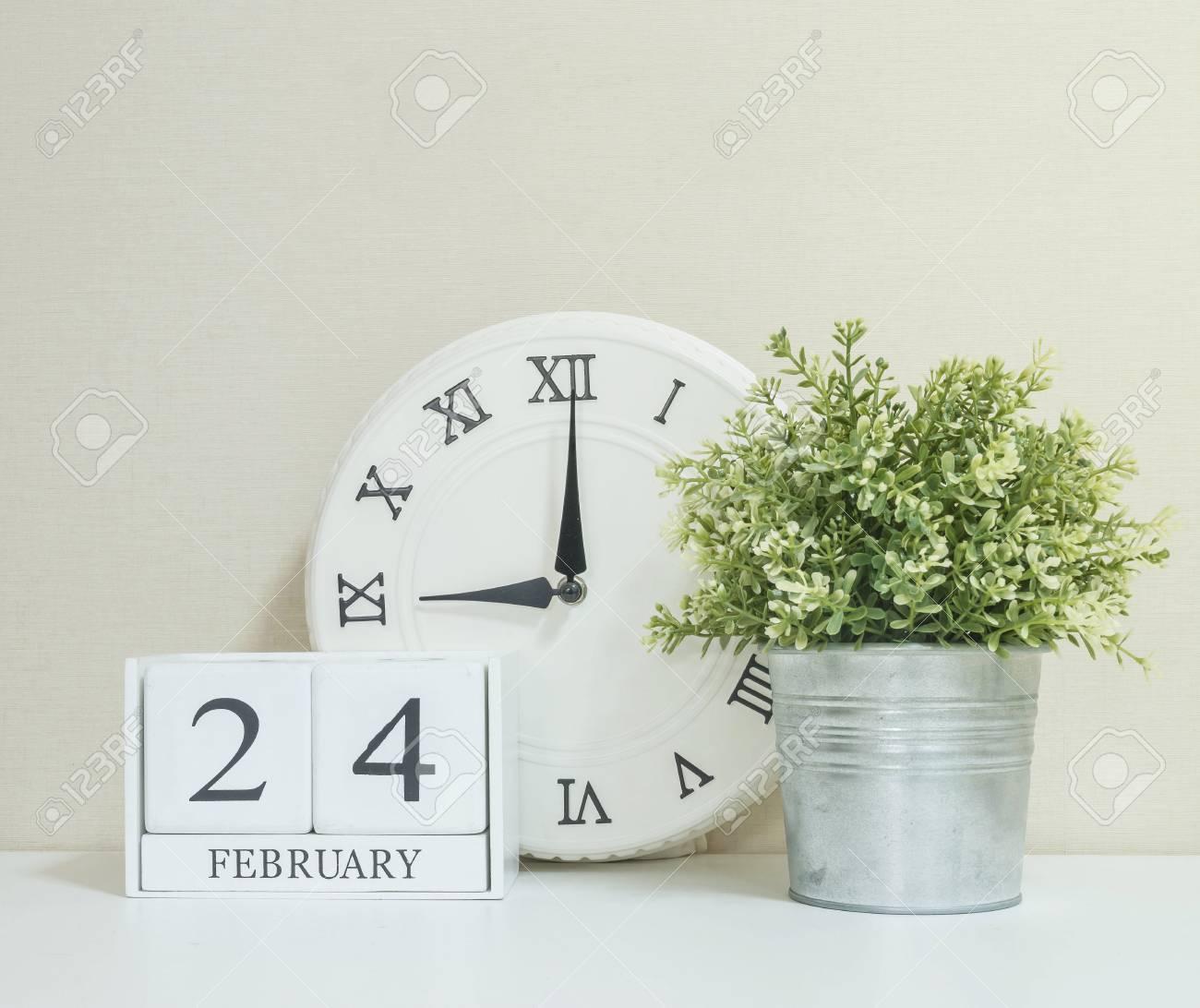 白い木製の机 カレンダーで選択と集中で質感のクリームの壁紙の背景に黒の 2 月 24 日単語の時計と工場と白い木製カレンダー の写真素材 画像素材 Image