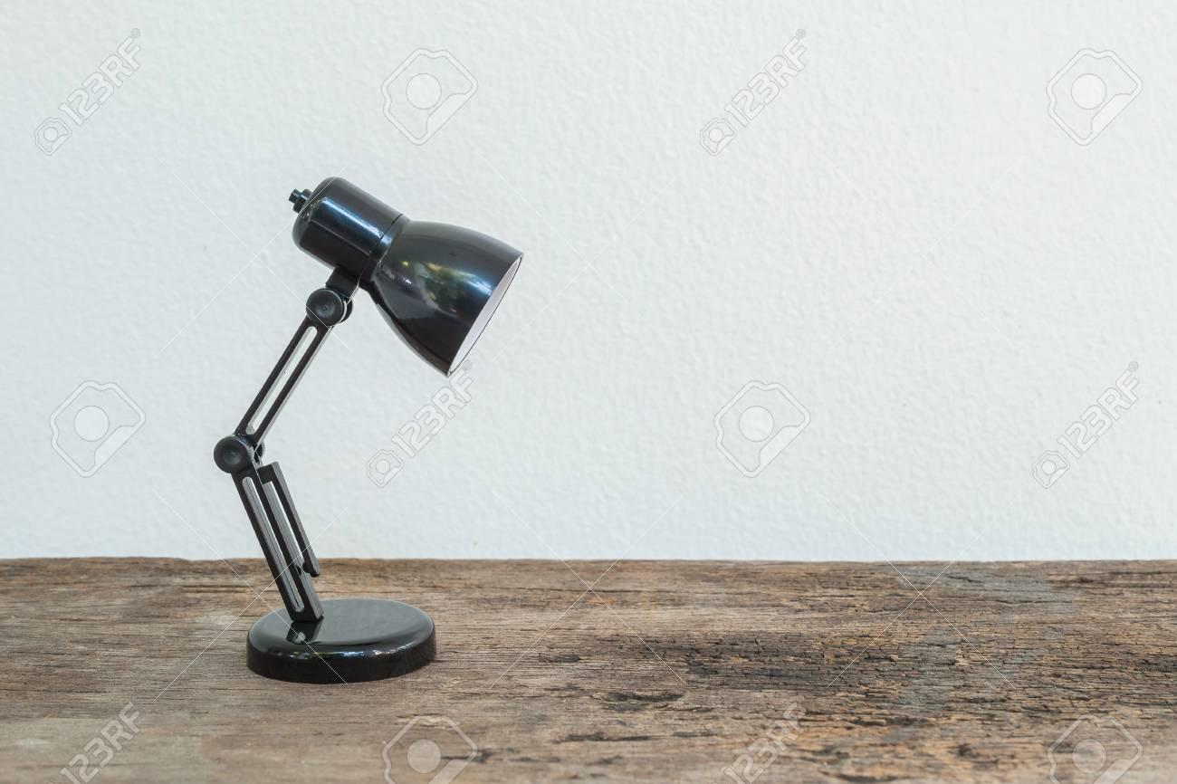 Closeup petite lampe sur bois bureau et mur de ciment blanc